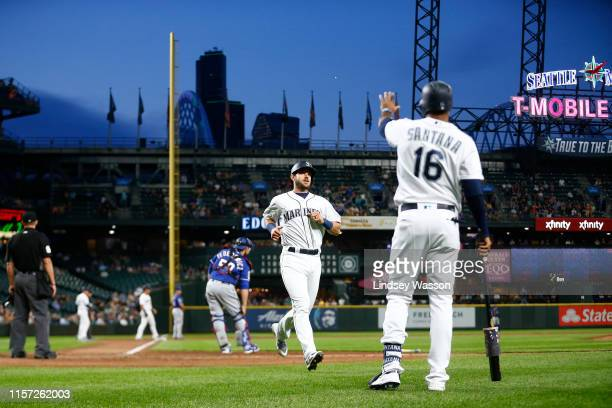 Austin Nola of the Seattle Mariners is greeted by Domingo Santana after scoring on a single by J.P. Crawford against the Texas Rangers in the sixth...