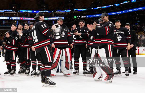 Austin Plevy of the Northeastern Huskies celebrates with the Beanpot trophy after a victory against the Boston College Eagles during NCAA hockey in...