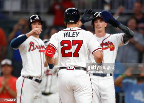 Austin Riley of the Atlanta Braves celebrates hitting a grand slam with teammates as he scores in the seventh inning of an MLB game against the...