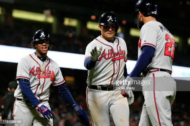 Austin Riley of the Atlanta Braves celebrates hitting a three run home run with Ronald Acuna Jr. #13 and Nick Markakis during the seventh inning...