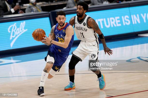 Austin Rivers of the Denver Nuggets drives against Kyrie Irving of the Brooklyn Nets in the first quarter at Ball Arena on May 08, 2021 in Denver,...