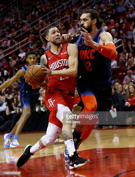 Austin Rivers of the Houston Rockets drives past Steven Adams of the Oklahoma City Thunder for a layup during the second quarter at Toyota Center on...