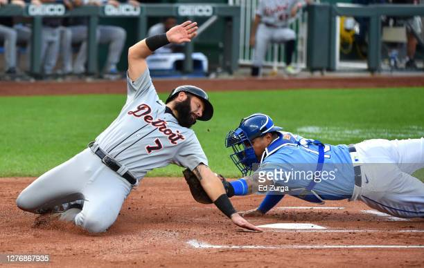 Austin Romine of the Detroit Tigers is tagged out as he tries to score against catcher Salvador Perez of the Kansas City Royals in the first inning...