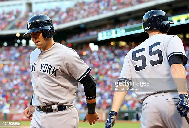 Austin Romine of the New York Yankees celebrates a run with Lyle Overbay against the Texas Rangers at Rangers Ballpark in Arlington on July 23 2013...