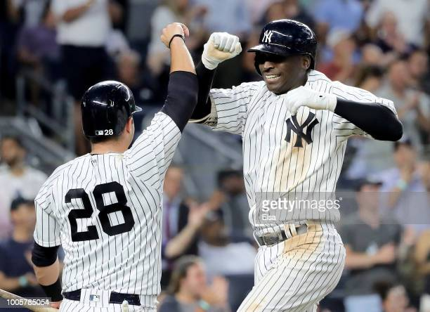 Austin Romine of the New York Yankees congratulates Didi Gregorius after he hit a three run home run in the fourth inning against the Kansas City...