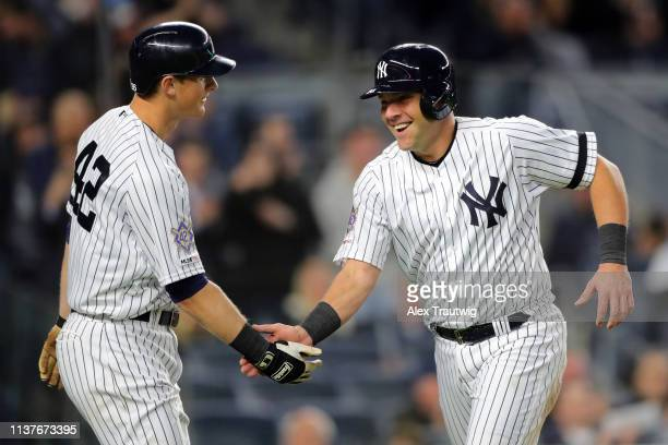 Austin Romine of the New York Yankees is greeted by teammate DJ LeMahieu after scoring a run in the fourth inning during the game between the Boston...
