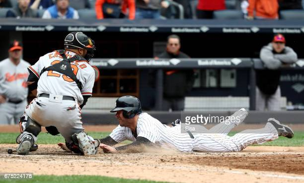 Austin Romine of the New York Yankees is out at home as catcher Welington Castillo of the Baltimore Orioles makes the out in the 10th inning on April...