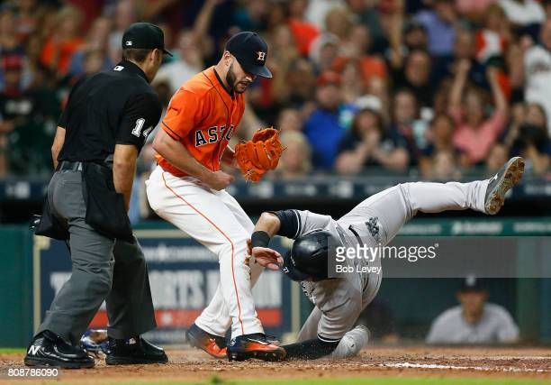 Austin Romine of the New York Yankees is tagged out by Lance McCullers Jr #43 of the Houston Astros as he attempts to score at Minute Maid Park on...