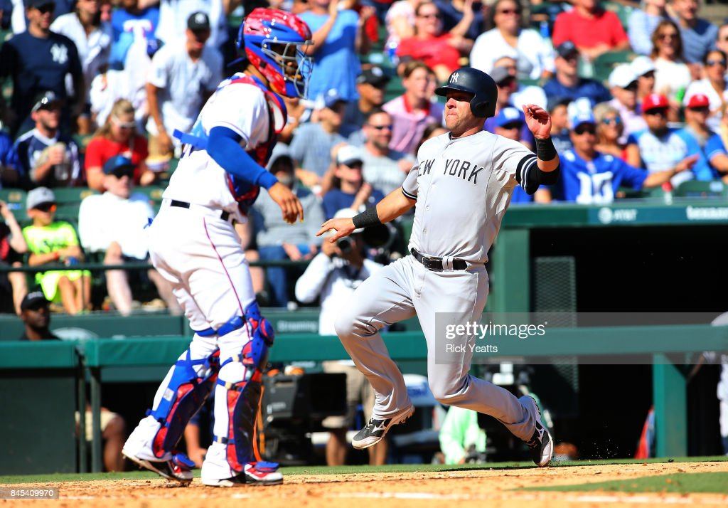 Austin Romine #27 of the New York Yankees scores against Robinson Chirinos #61 of the Texas Rangers in the fifth inning at Globe Life Park in Arlington on September 10, 2017 in Arlington, Texas.