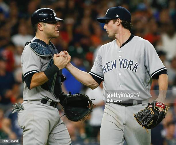 Austin Romine of the New York Yankees shakes hands with Bryan Mitchell after the final out against the Houston Astrosat Minute Maid Park on June 30...