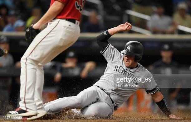Austin Romine of the New York Yankees slides safely into home plate after a wild pitch by the Minnesota Twins during the tenth inning of the game on...