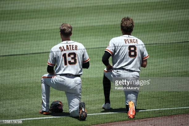 Austin Slater and Hunter Pence of the San Francisco Giants kneel during the national anthem before the game against the Los Angeles Dodgers at Dodger...