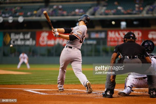 Austin Slater of the San Francisco Giants hits a two RBI single during the first inning against the Colorado Rockies at Coors Field on September 6...