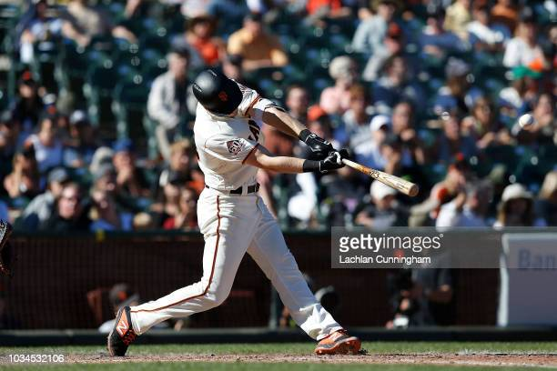 Austin Slater of the San Francisco Giants hits an RBI single in the bottom of the eighth inning against the Colorado Rockies at ATT Park on September...