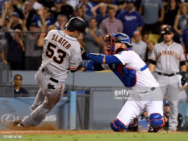 Austin Slater of the San Francisco Giants is tagged out by Yasmani Grandal of the Los Angeles Dodgers to end the top of the ninth inning at Dodger...