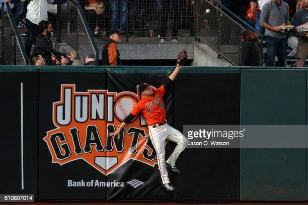 Austin Slater of the San Francisco Giants is unable to catch a fly ball hit for a home run by JT Realmuto of the Miami Marlins during the fifth...