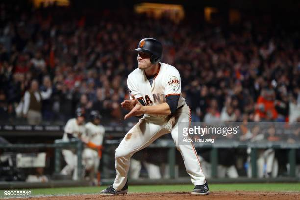 Austin Slater of the San Francisco Giants reacts after scoring in the seventh inning during a game against the Colorado Rockies at ATT Park on...