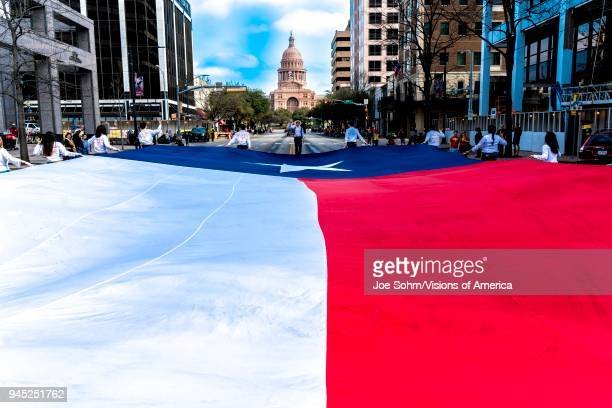Austin Texas University of Texas students carry Texas flag down Congress Avenue for the annual Texas Independence Day parade to the Texas Capitol An...