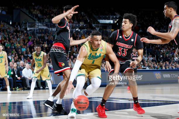 Austin Torres of the Notre Dame Fighting Irish dribbles against defense from Jordan Nwora and Anas Mahmoud of the Louisville Cardinals in the first...