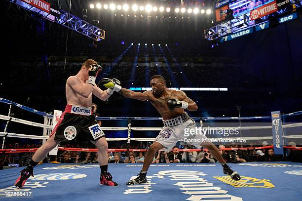 Austin Trout throws a punch Canelo Alvarez of Mexico during the WBC WBA and Vacant Ring Magazine Super Welterweight Title Fight at Alamodome on April...