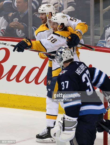 Austin Watson and Ryan Hartman of the Nashville Predators celebrate a third period goal as goaltender Connor Hellebuyck of the Winnipeg Jets looks on...