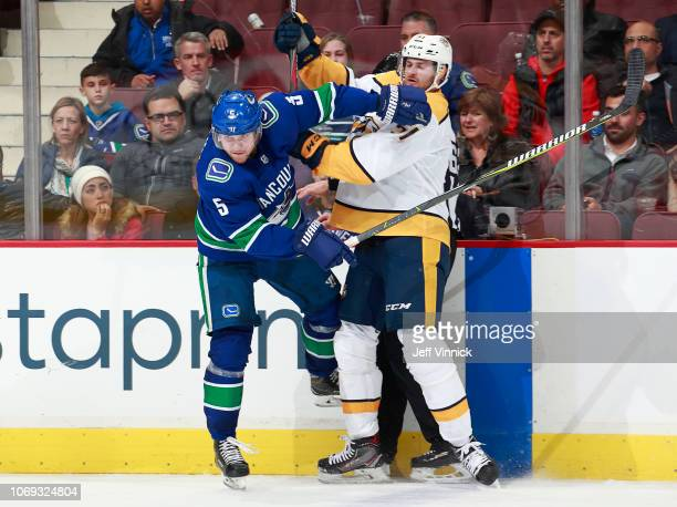 Austin Watson of the Nashville Predators checks Derrick Pouliot of the Vancouver Canucks during their NHL game at Rogers Arena December 6, 2018 in...