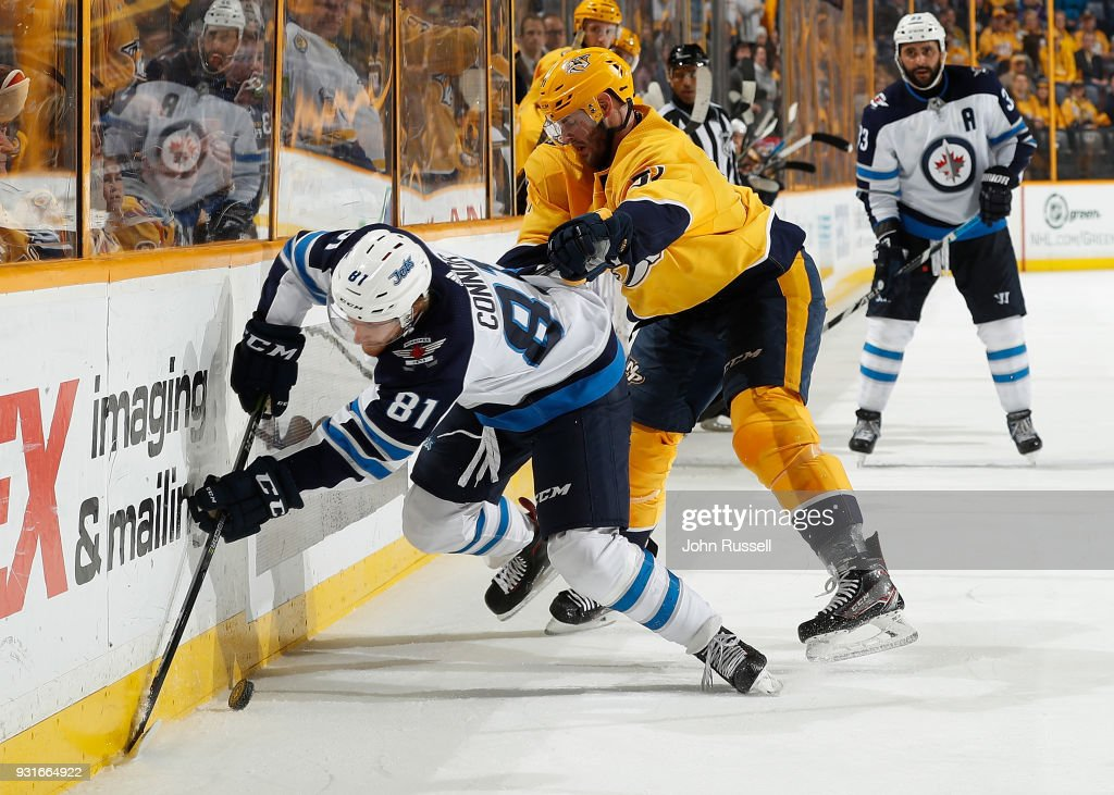 Austin Watson #51 of the Nashville Predators checks Kyle Connor #81 of the Winnipeg Jets during an NHL game at Bridgestone Arena on March 13, 2018 in Nashville, Tennessee.