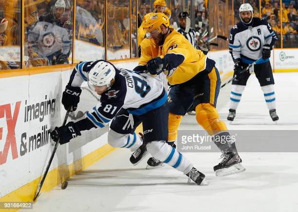 Austin Watson of the Nashville Predators checks Kyle Connor of the Winnipeg Jets during an NHL game at Bridgestone Arena on March 13 2018 in...