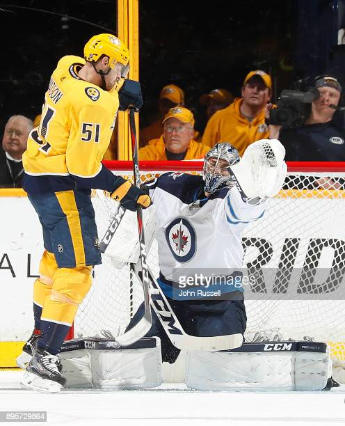 Austin Watson of the Nashville Predators deflects a shot against Connor Hellebuyck of the Winnipeg Jets during an NHL game at Bridgestone Arena on...