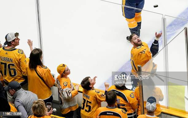 Austin Watson of the Nashville Predators toss a puck to a fan during warmups prior to Game One of the Western Conference First Round against the...