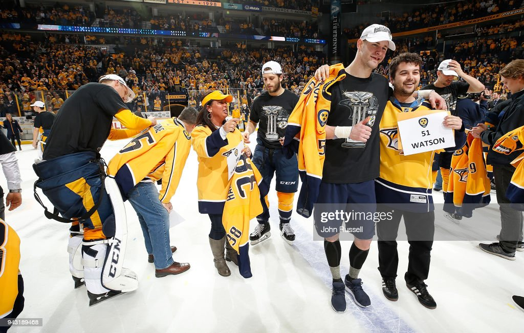 Austin Watson #51, Ryan Hartman #38 and Pekka Rinne #35 of the Nashville Predators give fans their jerseys after a 4-2 win against the Columbus Blue Jackets to finish the regular season as the Presidents' Cup Trophy winner at Bridgestone Arena on April 7, 2018 in Nashville, Tennessee.
