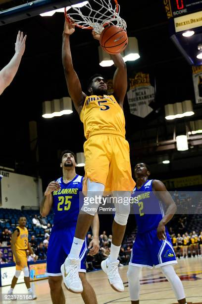 Austin Williams of the Drexel Dragons dunks against Skye Johnson and Ryan Allen of the Delaware Fightin Blue Hens during the second half at the...