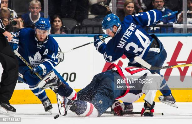 Auston Matthews and Morgan Rielly of the Toronto Maple Leafs battle with Lars Eller of the Washington Capitals during the third period in Game Four...