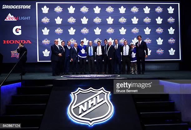 Auston Matthews celebrates onstage with Toronto Maple Leafs General Manager Lou Lamoriello and Mike Babcock after being selected first overall during...
