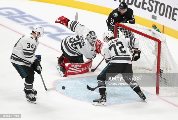 Auston Matthews of the Toronto Maple Leafs and Thomas Chabot of the Ottawa Senators look to clear the puck from the crease area as goaltender Jimmy...