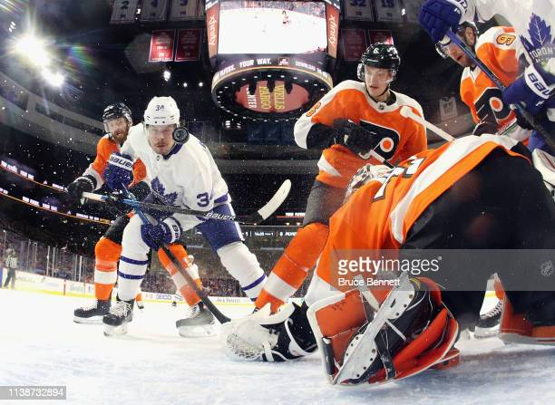 Auston Matthews of the Toronto Maple Leafs attempts to control the puck in front of Carter Hart of the Philadelphia Flyers during the first period at...