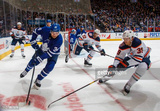 Auston Matthews of the Toronto Maple Leafs battles for the puck against Alex Chiasson of the Edmonton Oilers during the second period at the...