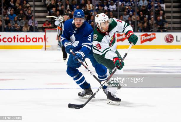 Auston Matthews of the Toronto Maple Leafs battles for the puck against Luke Kunin of the Minnesota Wild during the second period at the Scotiabank...