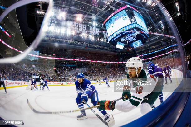 Auston Matthews of the Toronto Maple Leafs battles for the puck against Jordan Greenway of the Minnesota Wild during the third period at the...