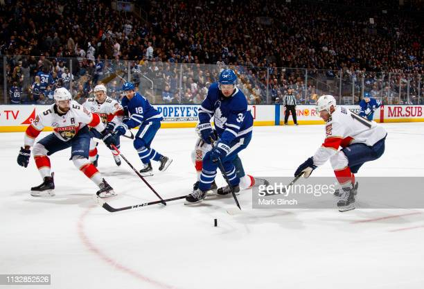 Auston Matthews of the Toronto Maple Leafs battles for the puck against Aleksander Barkov of the Florida Panthers and Aaron Ekblad during the second...