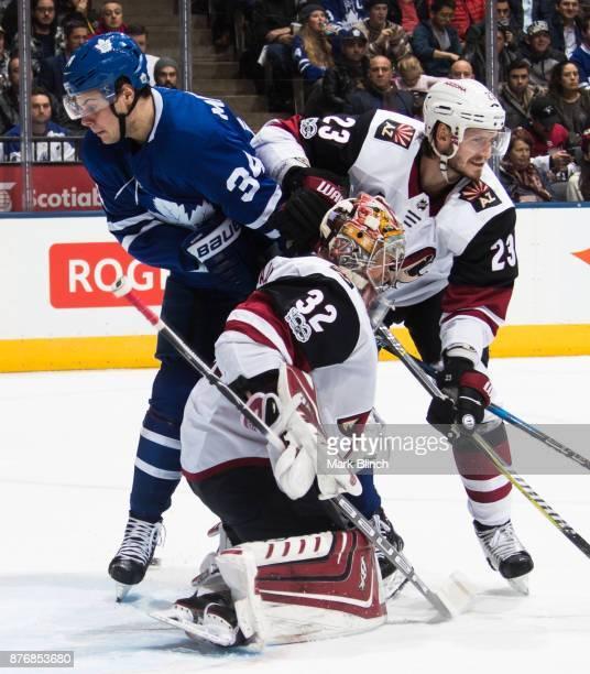 Auston Matthews of the Toronto Maple Leafs battles with Oliver EkmanLarsson of the Arizona Coyotes as Antti Raanta of the Arizona Coyotes follows the...