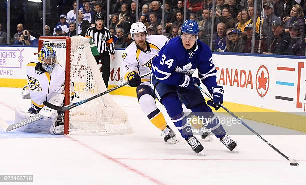 Auston Matthews of the Toronto Maple Leafs carries the puck past Yannick Weber and Marek Mazanec of the Nashville Predators during the first period...