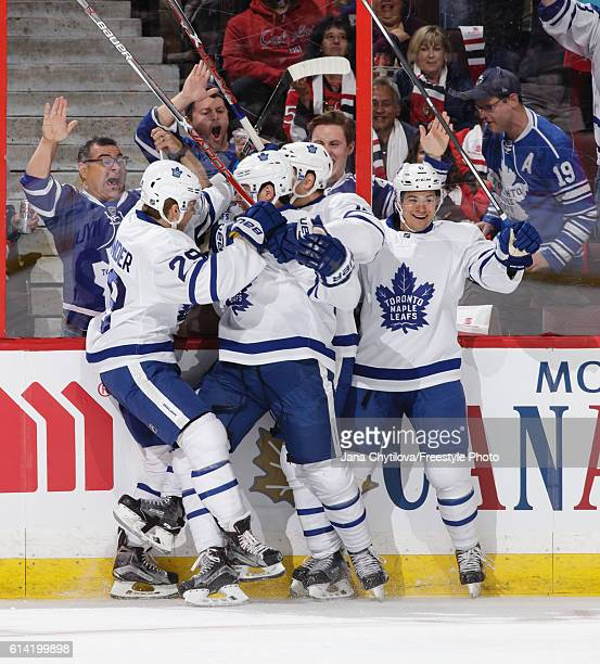 Auston Matthews of the Toronto Maple Leafs celebrates his first NHL goal in his first career NHL game with team mates William Nylander Zach Hyman and...