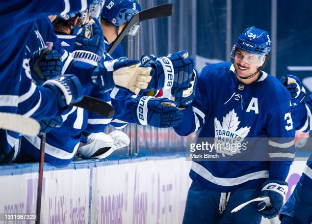 Auston Matthews of the Toronto Maple Leafs celebrates his hat trick goal with the bench against the Ottawa Senators during the second period at the...