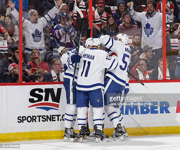 Auston Matthews of the Toronto Maple Leafs celebrates his second career NHL goal against the Ottawa Senators with team mates Zach Hyman and Martin...