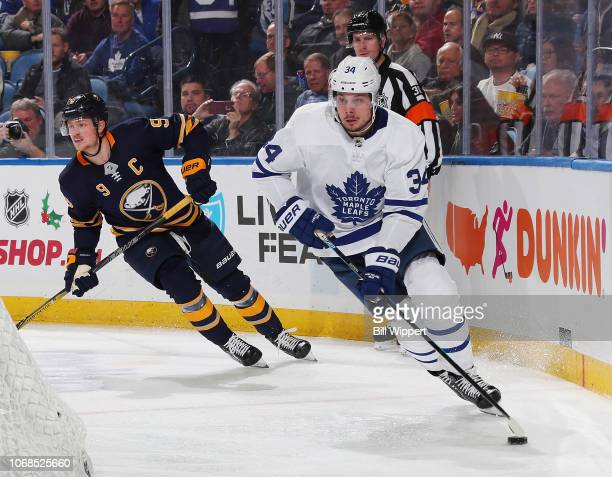 Auston Matthews of the Toronto Maple Leafs controls the puck against Jack Eichel of the Buffalo Sabres during an NHL game on December 4 2018 at...