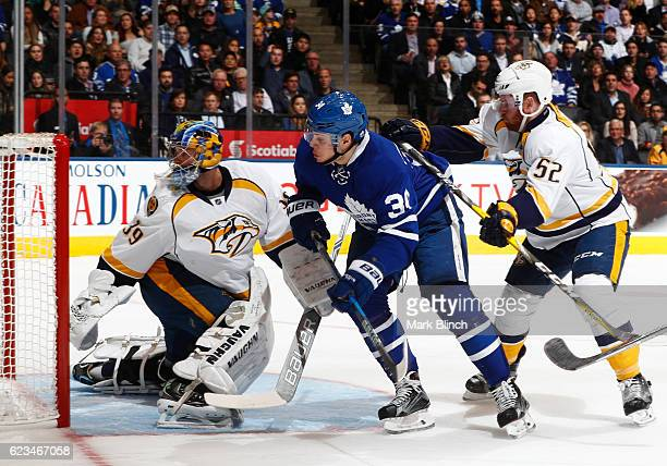 Auston Matthews of the Toronto Maple Leafs follows the puck with Matt Irwin and goalie Marek Mazanec of the Nashville Predators during the first...