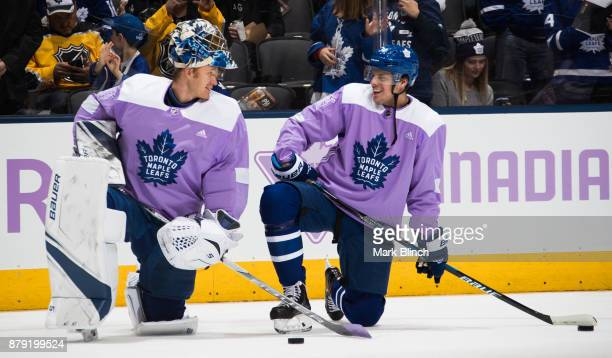 Auston Matthews of the Toronto Maple Leafs laughs with teammate Frederik Andersen during warm up wearing lavender jerseys as part of the Hockey...