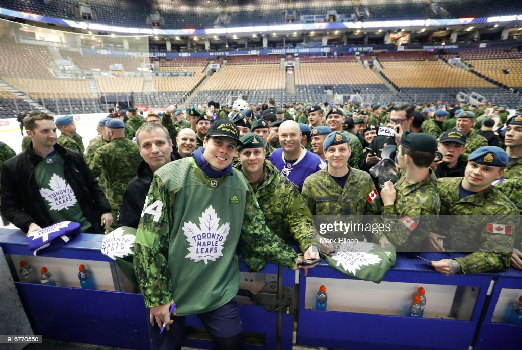 Auston Matthews #34 of the Toronto Maple Leafs signs autographs and stands for pictures with members of the Canadian Armed Forces at the Air Canada Centre on February 10, 2018 in Toronto, Ontario, Canada.