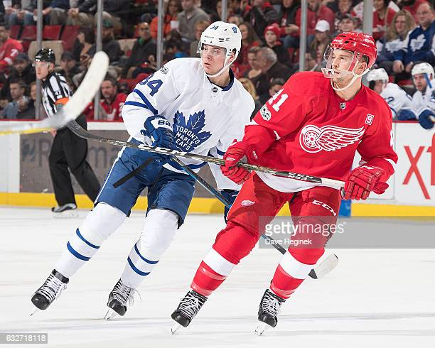Auston Matthews of the Toronto Maple Leafs skates up ice with Luke Glendening of the Detroit Red Wings during an NHL game at Joe Louis Arena on...